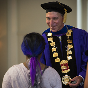 President Messitte presents a Class of 2020 coin to an incoming first-year student during Matriculation Convocation.