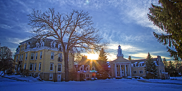 The sun sets behind Bartlett Hall and Harwood Memorial Union.
