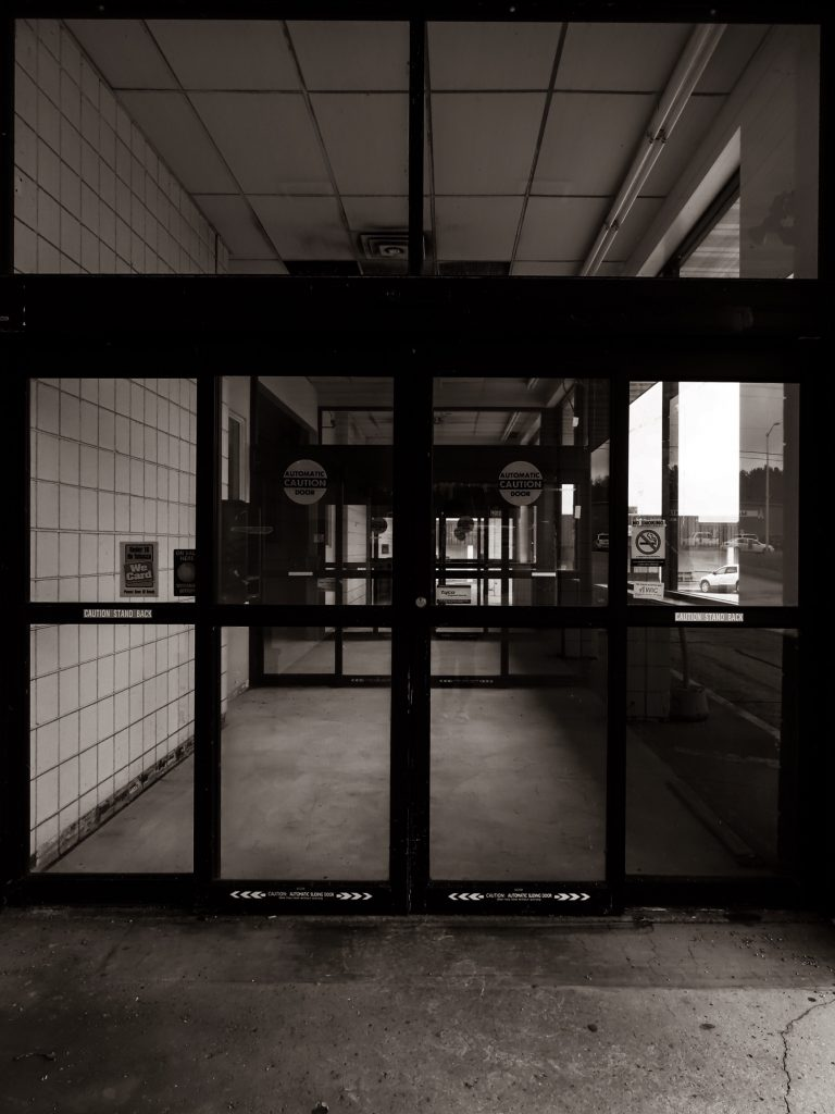 black and white empty hallway with glass door in front of it