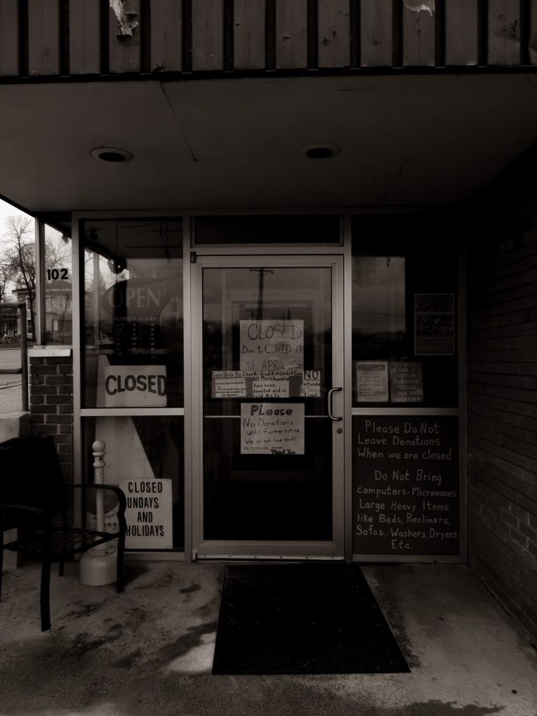 black and white store front photo with closed sign on door