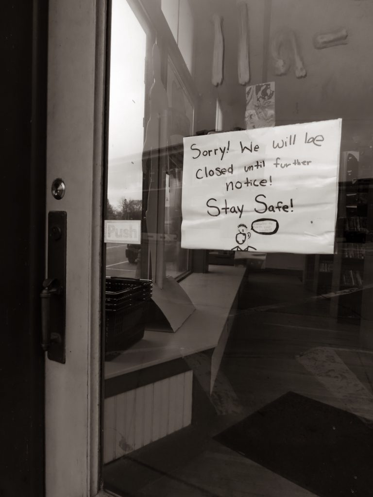 black and white photo with handwritten sign in store window