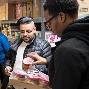 Zaeem Kitsos and DeShawn Thomas help stock shelves at Traded Treasures and Community Food Pantry as part of community service work done on MLK Day.