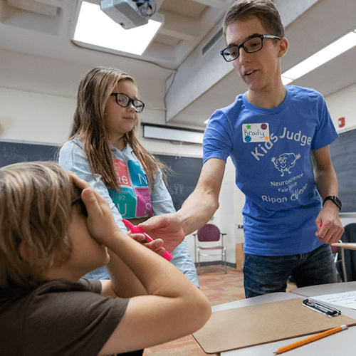 Ripon College sophomore Brady Spors teaches a pair of grade school students about the brain and five senses.