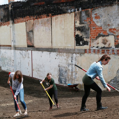 Photo of three female students raking ground