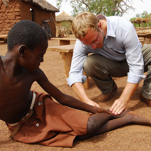 Adam Weiss, helping a patient suffering with Guinea worm.
