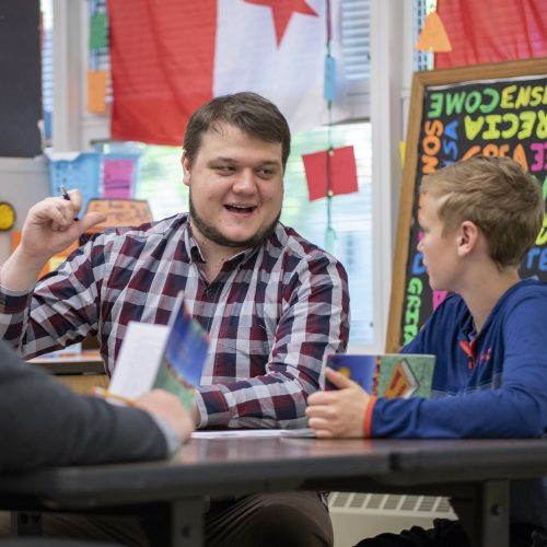 Photo of Josh LeGreve with students in the classroom