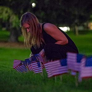 A student places flags in the ground to commemorate lives lost Sept. 11, 2001.