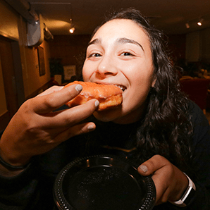 A student takes a bite out of a donut as part of Alpha Chi Omega's