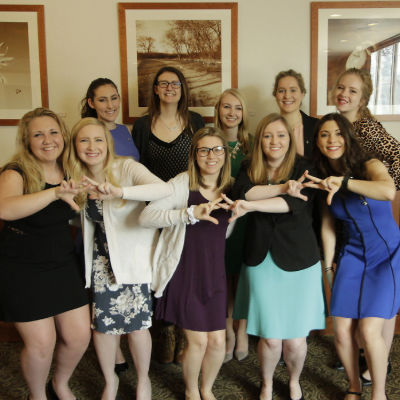 Sisters of Alpha Chi Omega throw their letters.