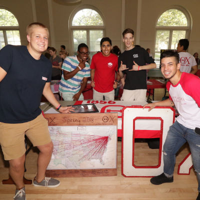 The brothers of Theta Chi pose at a table.