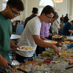 Students browse the wide selection of food options provided by local church members during the annual church potluck dinner.