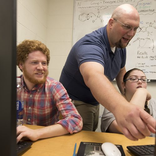 Joe Scanlong and students working at computer
