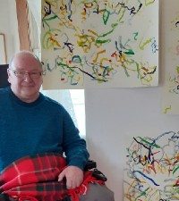 man named jon next to colorful art pieces
