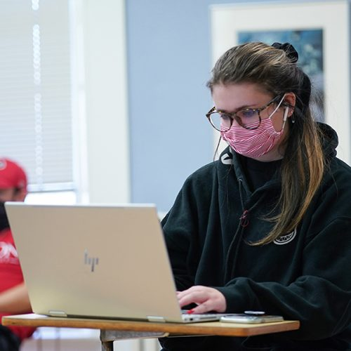 Jacey Musha '24 wearing a mask while working on a laptop computer