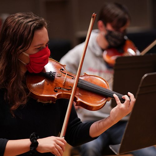Masked student playing a violin