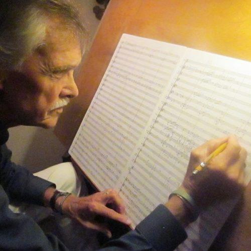 John Harmon composing at the piano